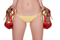 Sexy and slim woman in yellow swimming panties with shoes on her hands. Royalty Free Stock Photo