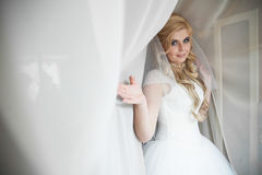 Sexy smiling blonde bride posing in wedding dress under white cu Stock Photography