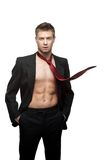 Sexy smiling businessman in red tie. Portrait of young caucasian sexy smiling man in black suit and red tie dressed over naked body Royalty Free Stock Photography