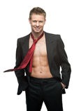 Sexy smiling businessman in red tie. Portrait of young caucasian sexy smiling man in black suit and red tie dressed over naked body Stock Photo