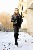 Blond smiling girl with gun Stock Photography