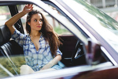 Sexy smiling girl with long hair resting in classic car Stock Photography