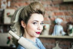 smiling girl with rolling pin on her shoulder in the kitchen. young woman blonde prepares dough in the kitchen royalty free stock photography