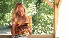 smiling woman eating vegetable at the beach stock footage