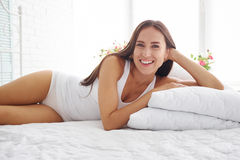 Sexy smiling woman in white underwear on white bed Stock Image