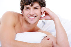 Sexy smiling young nude man lying in bed Royalty Free Stock Image
