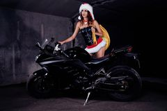 Snow maiden at sport bike. Girl in Santa Claus costume stands near a sport motorcycle royalty free stock image