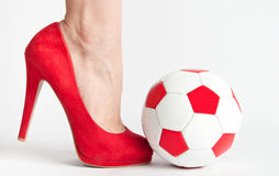 Sexy soccer. Woman leg in high heel shoe punch a soccer ball Stock Images