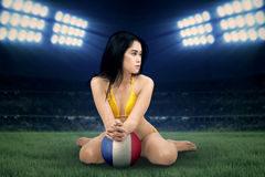 Sexy soccer fan with ball at the field Royalty Free Stock Photography
