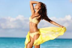 Sexy Sonnenbräunebikini-Körperfrau, die auf Strand sich entspannt Stockbild