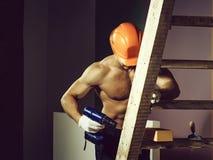 Sexy spiermensenbouwer op ladder royalty-vrije stock fotografie