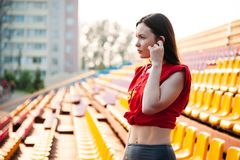 sport girl posing at stadium nad listening to music on headphones. Fitness girl with a sports figure in leggings and red top royalty free stock image