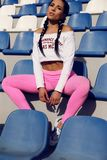 Sexy sportive girl with dark hair in sport clothes posing at sta. Fashion outdoor photo of sexy sportive girl with dark hair in sport clothes posing at stadium Royalty Free Stock Image