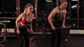 Sexy sports couple with bodybars in the gym. Sport concept. Young sexy woman and strong muscular man doing exercises at the gym stock footage