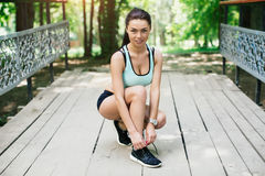 sports girl ties the laces on shoes Stock Photo