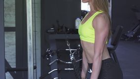 Sexy sportswoman with perfect body doing rope pull down exercise. Sliding shot of a young healthy sportswoman with perfect toned body training at the gym, doing stock footage