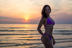 Sexy sporty woman in bikini over sea background. At sunset Stock Photo