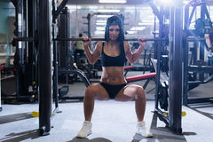Sexy sporty woman doing power fitness exercise at sport gym. Beautiful girl working out in gym. Stock Images
