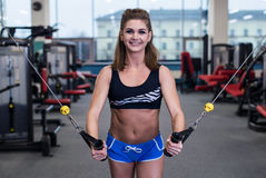 Sexy sporty woman doing power fitness exercise at sport gym. Beautiful girl working out in gym. Royalty Free Stock Images