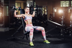 Sexy sporty woman exercising in gym with dumbbells. Sexy sporty woman resting after exercising in gym with dumbbells Royalty Free Stock Image