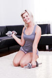 Sexy sporty woman is using dumbbells at home. Attractive sporty woman is gymnastics at home Stock Photos