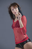 Sexy spy with gun. Young woman in sexy clothes posing with gun over grey background Royalty Free Stock Photo
