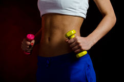 Sexy stomach. Girl's muscled stomach during dumbbells workout - angle view Stock Photo