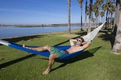 Sexy Strandkerl, der in einer Hängematte sich bräunt stockfotos