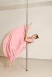 Sexy strip dancer exercising with pole in studio Stock Photos
