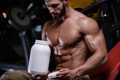 Strong bodybuilder athletic men pumping up muscles with dum. Strong bodybuilder athletic fitness man pumping up abs muscles workout bodybuilding concept stock images
