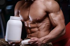 Sexy strong bodybuilder athletic men pumping up muscles with dum Royalty Free Stock Photos