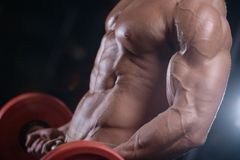 Sexy strong bodybuilder athletic men pumping up muscles with dum. Sexy strong bodybuilder athletic fitness man pumping up abs muscles workout bodybuilding Stock Photos