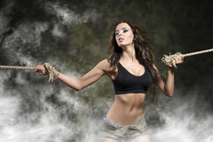 Sexy strong girl tied by rope in the smoke Stock Photo