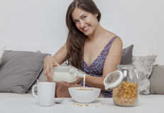 Sexy student in night pours milk on her corn flakes Royalty Free Stock Photos