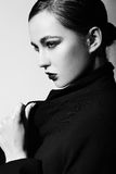 Sexy stylish brunette Caucasian young woman model with bright green makeup, with red lips,  with perfect clean skin in overcoat in Royalty Free Stock Photos