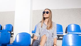 Portrait of sexy stylish young woman posing on empty stadium seats. Sexy stylish young woman posing on empty stadium seats Stock Images