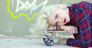 Sexy sultry young blond woman. With a lip piercing lying relaxing on her skate board at the skate park looking at the camera with a serious expression stock footage