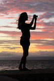 Sunset Silhouette of Woman Taking Photos royalty free stock images