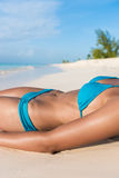 Sexy suntan bikini body woman sunbathing on beach Stock Images