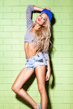Sexy suntan girl in short jeans shorts against green brick wall Royalty Free Stock Photos