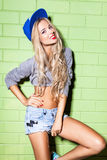 Sexy suntan girl in short jeans shorts against green brick wall Royalty Free Stock Photo