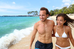 suntan interracial couple walking on beach Royalty Free Stock Images