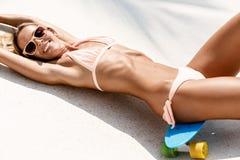 Sexy suntanned Dame, die auf dem blauen Pennybrett im Park liegt Stockfotos