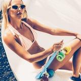 Sexy suntanned Dame, die mit blauem Pennybrett auf dem Strand sitzt Stockfotografie