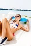Sexy suntanned Dame, die mit blauem Pennybrett auf dem Strand sitzt Lizenzfreie Stockbilder
