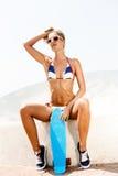 Sexy suntanned Dame, die mit blauem Pennybrett auf dem Strand sitzt Lizenzfreies Stockbild