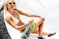 Sexy suntanned Dame, die mit blauem Pennybrett auf dem Strand sitzt Stockbilder