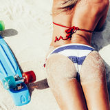 Sexy suntanned lady with the blue penny board lying on the beach Royalty Free Stock Photography