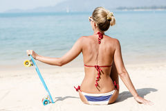 Sexy suntanned lady with the blue penny board rests on the beach Stock Photography