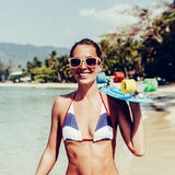 Sexy suntanned lady with the blue penny board walks along the be Stock Images